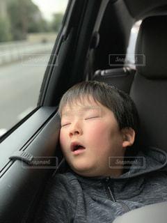 車の後部座席で寝ている少年の写真・画像素材[1805570]