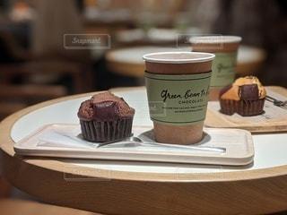 テーブルの上に座っているチョコレートケーキの写真・画像素材[3108887]
