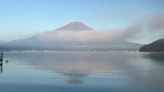 背景に山のある水の体の写真・画像素材[3637272]