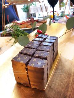 木製テーブルの上に座っているケーキの写真・画像素材[1682949]