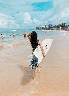浜辺に立っているサーファーの写真・画像素材[3065266]
