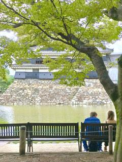 松本城、お堀の脇のベンチでくつろぐカップルの写真・画像素材[1454009]