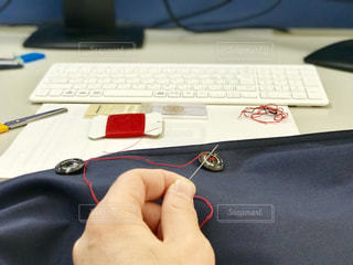 コートのボタンが取れてしまったので、オフィスのデスクで裁縫チーチク。の写真・画像素材[1717061]