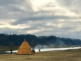 曇り空の下、テント前で焚き火をして暖をとるの写真・画像素材[1785106]