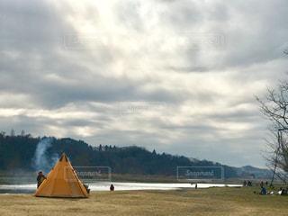 曇り空の下、テント前で焚き火をして暖をとるの写真・画像素材[1785107]