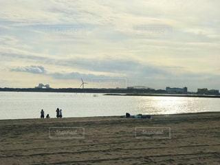 夕陽が輝く葛西海浜公園の砂浜で遊ぶ人影の写真・画像素材[2893346]