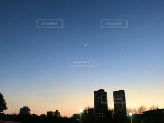 夕暮れに浮かぶ高層ビルのシルエットと月の写真・画像素材[4057248]