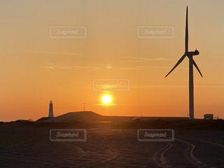 夕日を背景にした風車の写真・画像素材[3064579]