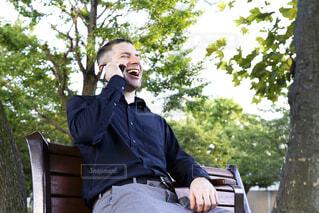 公園のベンチで電話しながら笑っている外国人男性の写真・画像素材[3820966]