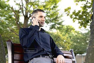 ベンチに座って電話している外国人男性の写真・画像素材[3820967]