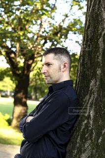 木に寄り掛かっている男性の写真・画像素材[3820976]
