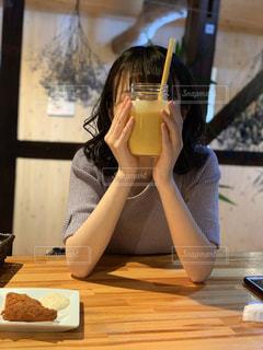 ワインを飲みながらテーブルに座っている女性の写真・画像素材[3072700]