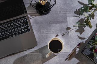 コーヒーを飲みながらデスクワークの写真・画像素材[3633025]