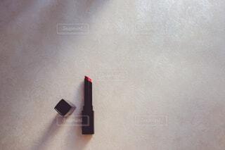 赤の口紅とビューラー。美容・ コスメ・メイクアップ。の写真・画像素材[3869363]
