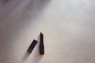 赤の口紅とビューラー。美容・ コスメ・メイクアップ。の写真・画像素材[3869362]