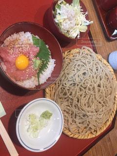 テーブルの上の皿の上に食べ物のボウルの写真・画像素材[1223116]