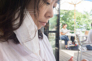 飲食中マスクを外した女性 夏のマスクの写真・画像素材[3990243]