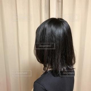 カーテンの前に立っている女性の写真・画像素材[3585578]