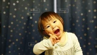 カーテンの前に座っている少女の写真・画像素材[3168263]