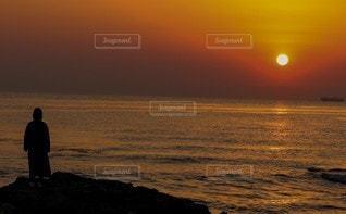 夕日を背景にビーチに立っているの写真・画像素材[3153170]