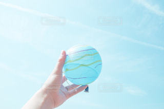 青い空に凧を持っている人の写真・画像素材[3134678]