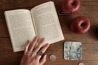 林檎とコースターと本とコインの写真・画像素材[4094965]