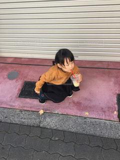 歩道に座っている人の写真・画像素材[3154495]