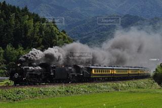 煙が出ている線路上の蒸気機関車の写真・画像素材[3161810]