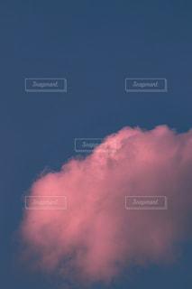 曇った青空を飛んでいる飛行機の写真・画像素材[3229691]