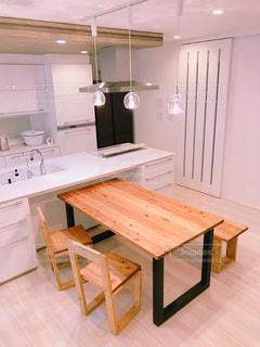 木製のテーブルと白いキッチンの写真・画像素材[3174495]
