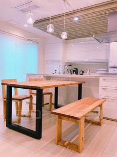 木製のテーブルと白いキッチンの写真・画像素材[3174482]