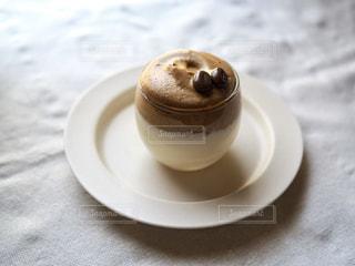 白い皿の上にのっているダルゴナミルクプリンのクローズアップの写真・画像素材[3171533]