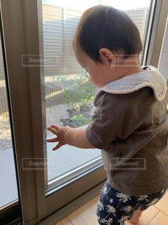 窓の前に立っている少年の写真・画像素材[3301909]