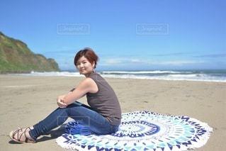 ビーチに座ってポーズをとる若い女性の写真・画像素材[3507147]