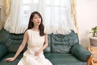 リビングのソファーでくつろぐ白いドレスを着た美しい女性の写真・画像素材[4109870]
