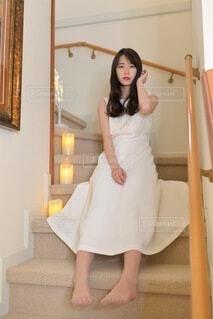 階段に座りポーズをとる白いドレスを着た美しい女性の写真・画像素材[4109883]