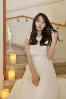 階段に座りポーズをとる白いドレスを着た美しい女性の写真・画像素材[4109882]