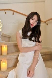 階段に座りポーズをとる白いドレスを着た美しい女性の写真・画像素材[4109884]