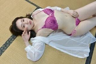 畳の上に横たわるピンクの下着姿の若い女性の写真・画像素材[4164812]