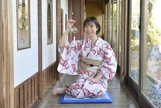 和室の廊下に座り風鈴を手に笑顔の浴衣女性の写真・画像素材[4189524]