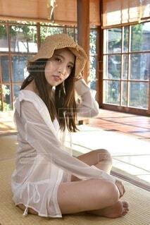 和室にて麦わら帽子を被った白い水着姿の若くスリムな女性の写真・画像素材[4209824]