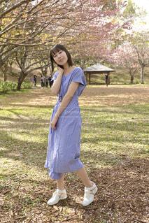 桜咲く公園でワンピースを着た若い笑顔の女性の写真・画像素材[4300759]