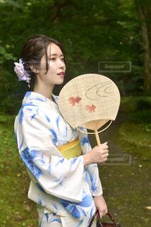 新緑の神社の境内とうちわを持つ美しい浴衣姿の若い女性の写真・画像素材[4619827]