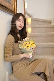 ヒマワリの花束を手に階段に座る若く美しい女性の写真・画像素材[4798684]