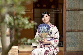 うちわ片手に町家の縁側にたたずむ浴衣姿の若い女性の写真・画像素材[4943441]