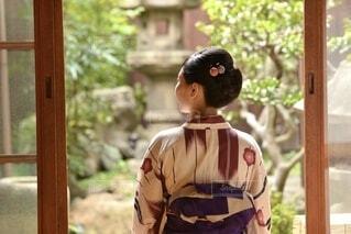 町家の縁側にたたずむ浴衣を着た若い女性の後ろ姿の写真・画像素材[4943559]