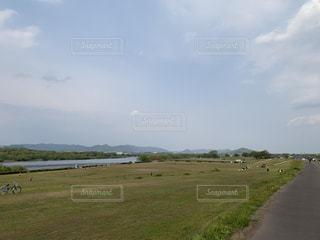 背景に木々のある大きな緑のフィールドの写真・画像素材[3179580]