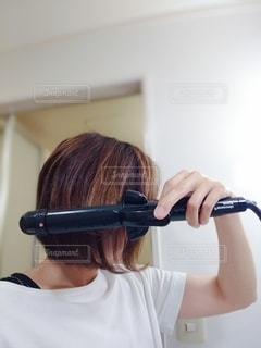 鏡の前に立ってカメラのポーズをとる女性の写真・画像素材[3327836]