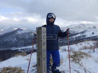 雪に覆われた山の上に立っている男の写真・画像素材[3207729]