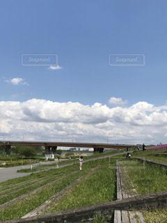 フィールドの近くの列車の線路を下って移動する列車の写真・画像素材[3203269]